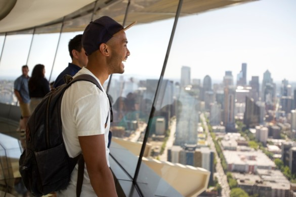 Guest enjoys views of downtown Seattle from the Space Needle glass floor - The Loupe