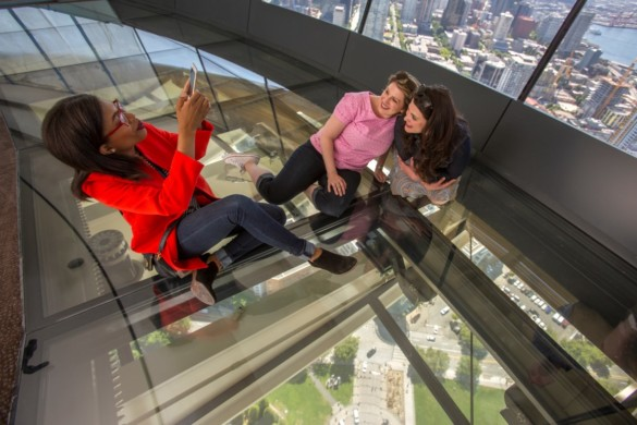 Guests pose for photo on The Loupe - first revolving glass floor. Courtesy of John Lok and Space Needle LLC