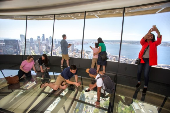 Guests take selfie on The Loupe - the world's first revolving glass floor. John Lok and Space Needle LLC