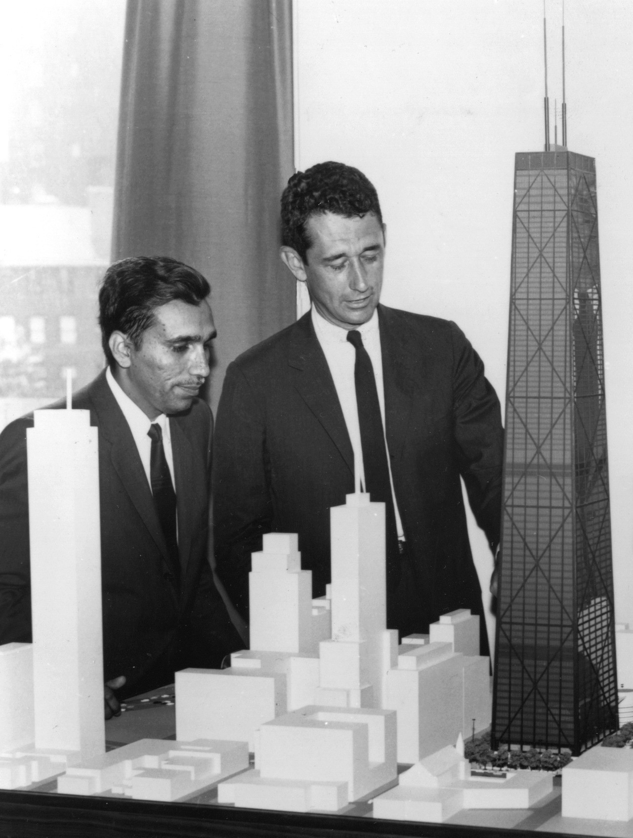 "Fazlur Khan (left) and Bruce Graham (right) look at a model of the John Hancock Center. ""The decision factor is ingrained in that picture — the way they look at the building together, the way they worked together, their back-and-forth dynamic,"" says Cashen. Image © SOM"