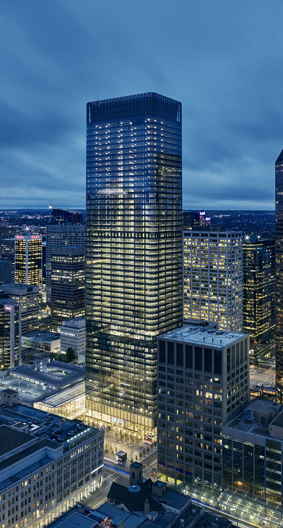 The exterior of Calgary's Brookfield Place all lit up at night. The project features lots of curved glass in what is currently the tallest tower in Calgary.
